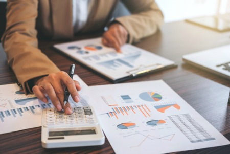 real estate market concept of graphs on table and person using calculator