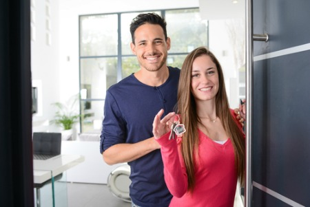 man and woman standing in doorway with house keys