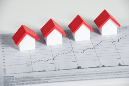 real estate market concept graph paper with small model houses on top